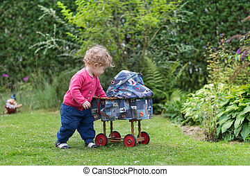 Adorable curly baby girl playing with a vintage toy stroller in