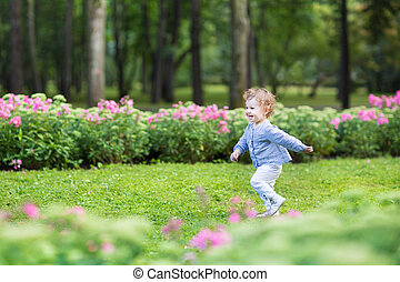 Adorable curly baby girl running in a beautiful park among...