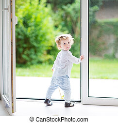 Adorable curly baby girl standing at a big glass door to the gar