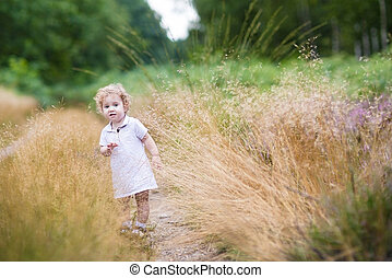 Adorable curly baby girl walking in high grass in an autumn park