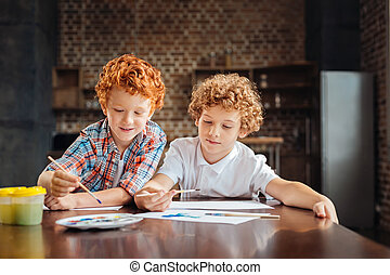 Adorable curly haired brother painting together