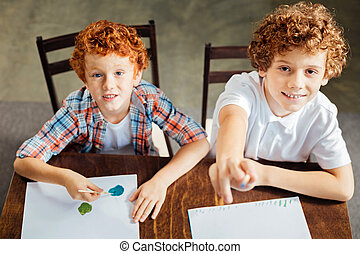 Adorable curly haired kids painting and looking into camera