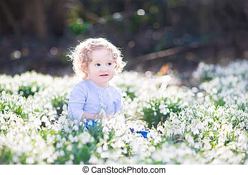 Adorable curly toddler girl playing with first spring flowers