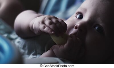 Adorable cute baby sit at children table eating pear. Blue eyes. Look in camera