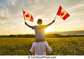 Adorable cute happy Caucasian boy holding Canadian flag on the father shoulder