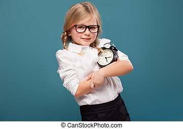 Adorable cute little girl in white shirt, glasses and black trousers hold alarm clock