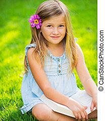 Adorable cute little girl reading book in the garden,...