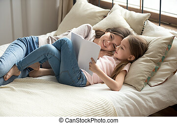 Adorable daughter and mother resting lying on bed reading book