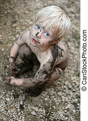 An adorable baby boy child with big blue eyes is looking sadly up at the camera as he sits on the ground covered in dirt and mud