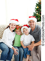 Adorable family at Christmas sitting in the living-room at home
