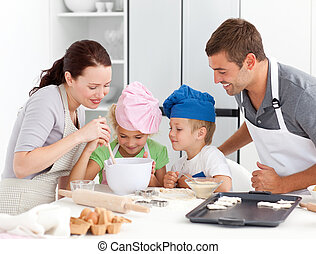 Adorable family baking together in the kitchen to make...