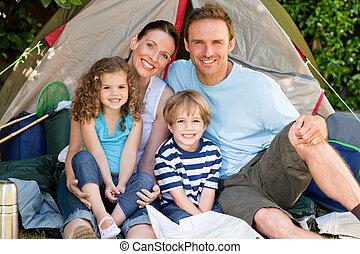 Adorable family camping in the garden