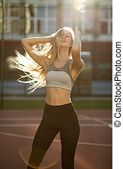 Adorable fitness girl with hair in wind wearing sport apparel, posing in rays of sun