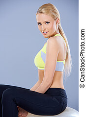 Adorable fitness woman sitting on ball