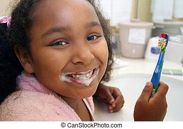 Adorable five year old African American Girl brushing her teeth in bathroom.