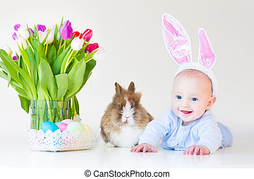 Adorable funny baby boy with bunny ears playing with a real rabb