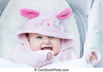 Adorable funny baby girl sitting in a stroller in a bunny snow s