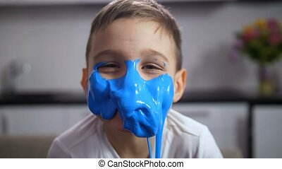 Adorable funny boy with face covered blue slime - Joyful...