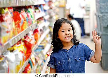 Adorable girl at shelves in supermarket