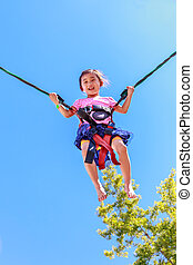 Adorable girl bungee jumping