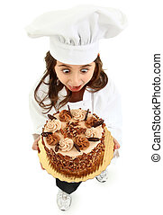 Adorable Girl Child in Chef Uniform holding Caramel Pecan Cake making funny hungry expression.