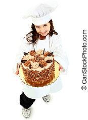 Adorable Girl Child in Chef Uniform holding Caramel Pecan Cake