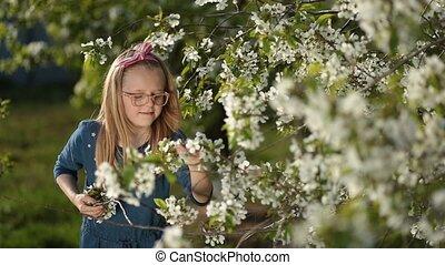 Adorable girl enjoying smell of spring garden