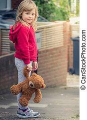 Adorable girl holding teddy bear
