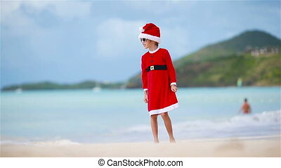 Adorable girl in Christmas hat on white beach during Xmas...