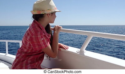 Adorable girl looking to the blue sea from yacht board -...