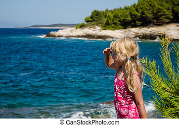 adorable girl looking to the sea