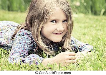adorable girl lying on grass