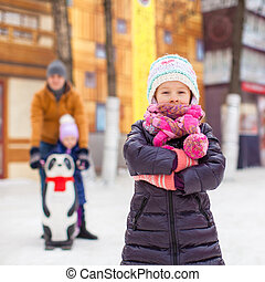 Adorable girl on skating rink, dad with little sister in the background