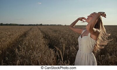 Adorable girl playing with hair in cereal field - Beautiful...