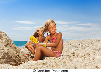 Adorable girl playing with sand at the beach