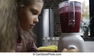 Adorable girl preparing fresh smoothie in blender - Portrait...