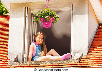 Adorable girl sitting on the ledge of attic window