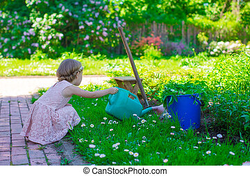 Adorable girl with a watering can at big green garden -...