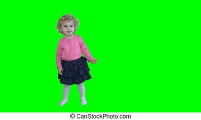 Adorable girl with blond curly hair dancing and jumping...
