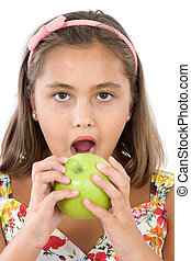 Adorable girl with flowered dress eating a apple