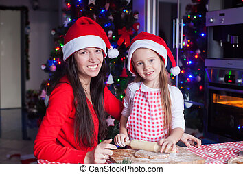 Adorable girl with her mother baking Christmas cookies in the kitchen