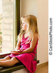 girl with long blond hair sitting by the window