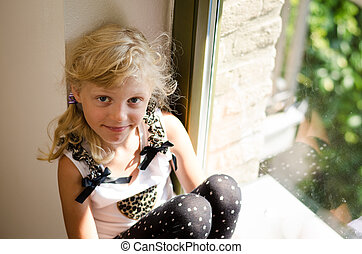 girl with long blond hair sitting in the window table