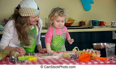 Adorable girl with mother cutting out dough for cookies with metal form