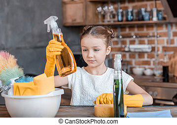 Adorable girl with spray bottles and different cleaning...