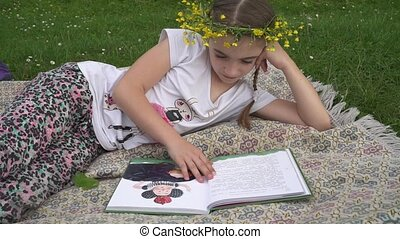 Adorable girl with wreath on the head reading book. Child lying in grass
