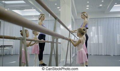 Adorable girls practice with teacher in ballet studio.