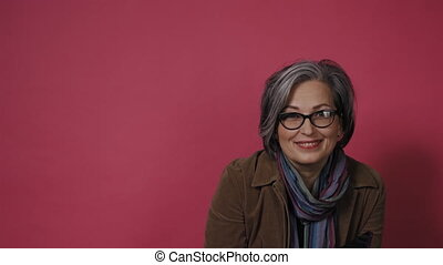 Adorable Gray-haired mature model in jeans posing on pink background. Pretty mature woman corrects eye glasses and look in to her smartphone. Prores 422.