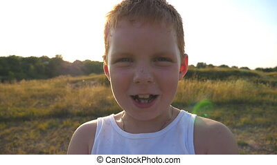 Adorable handsome baby looking into camera with joyful smile. Close up emotions of male child with glad expression on face. Portrait of happy red hair boy with freckles laughs outdoor. Slow motion