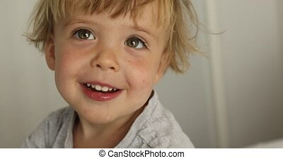 Adorable happy baby boy is looking at camera